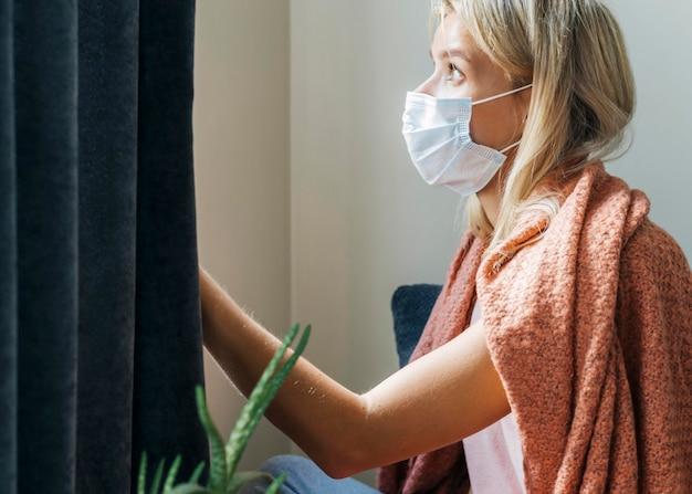 Widok z boku kobiety w domu noszącej maskę medyczną podczas pandemii
