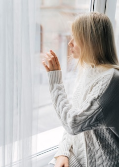 Widok z boku kobiety w domu podczas pandemii, patrząc przez okno