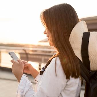 Widok z boku kobiety w kapeluszu za pomocą smartfona podczas samotnej podróży