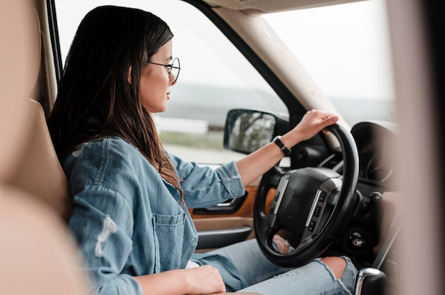 Widok z boku kobiety w okularach podróżujących samotnie samochodem