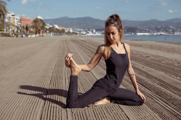 Widok z boku kobiety w pozie jogi na plaży