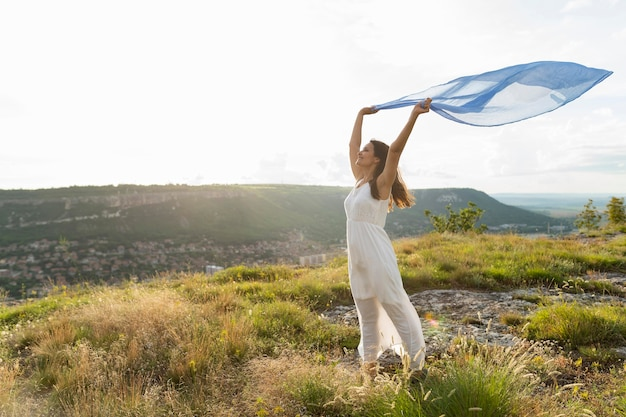 Widok z boku kobiety w przyrodzie z szalikiem na wietrze