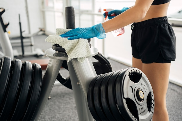 Widok z boku kobiety w rękawiczkach do dezynfekcji wyposażenia siłowni