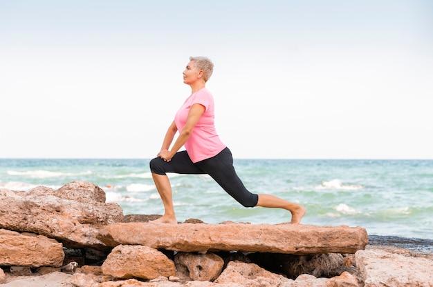 Widok z boku kobiety w średnim wieku robi joga na plaży