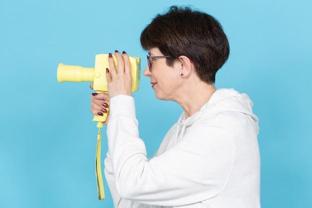 Widok z boku kobiety w średnim wieku z krótką fryzurą w swetrze i okularach trzymającej żółtą kamerę filmową vintage na niebieskiej powierzchni. koncepcja nagrywania wideo