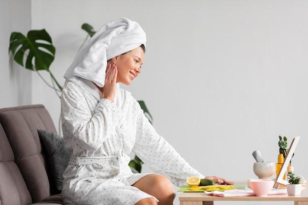Widok z boku kobiety w szlafroku przy użyciu produktów do pielęgnacji skóry