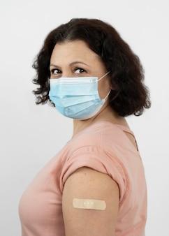 Widok z boku kobiety z bandażem na ramieniu po szczepieniu