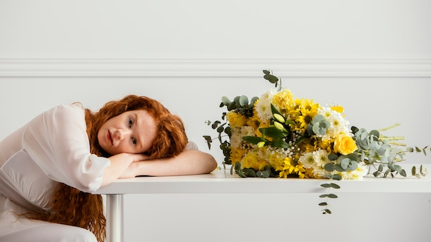 Widok z boku kobiety z bukietem wiosennych kwiatów na stole