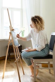 Widok z boku kobiety z kręconymi włosami, malowanie w domu