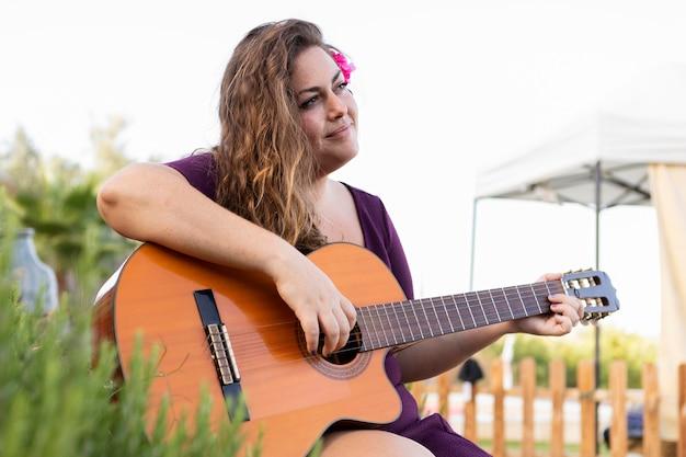 Widok z boku kobiety z kwiatem we włosach, gra na gitarze
