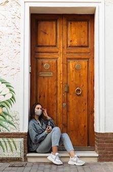 Widok z boku kobiety z maską i aparatem obok drzwi na zewnątrz