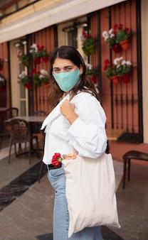 Widok z boku kobiety z maską i torby na zakupy na zewnątrz