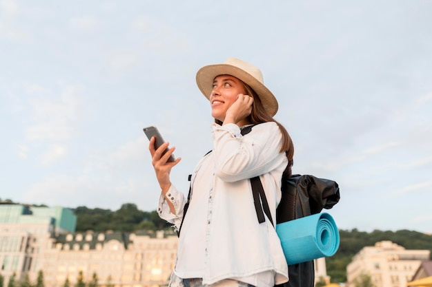 Widok z boku kobiety z podróży plecakiem i smartfonem