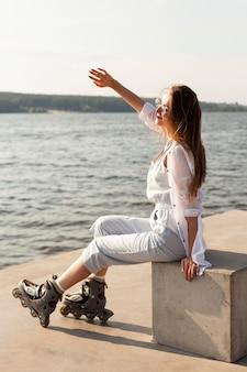 Widok z boku kobiety z rolkami osłaniającymi twarz przed słońcem nad jeziorem