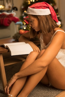 Widok z boku kobiety z santa hat czytając książkę na boże narodzenie