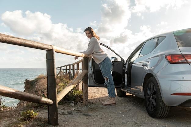 Widok z boku kobiety z widokiem na plażę z jej samochodu