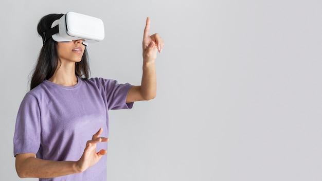Widok z boku kobiety za pomocą zestawu słuchawkowego wirtualnej rzeczywistości z miejsca na kopię