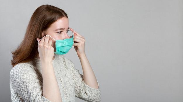 Widok z boku kobiety zakładającej maskę medyczną z miejsca na kopię