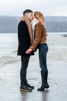 Widok z boku kochającej się pary nad jeziorem zimą