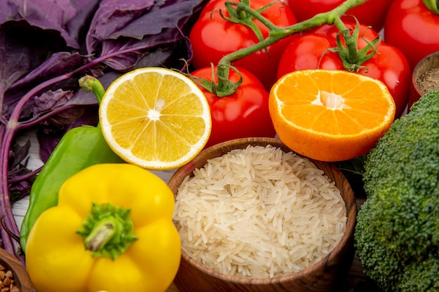 Widok z boku kolekcji świeżych warzyw i przypraw na białym stole