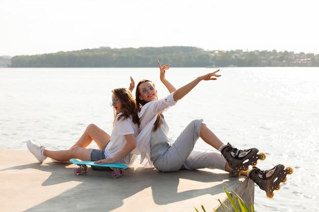 Widok z boku koleżanek z deskorolką i rolkami nad jeziorem