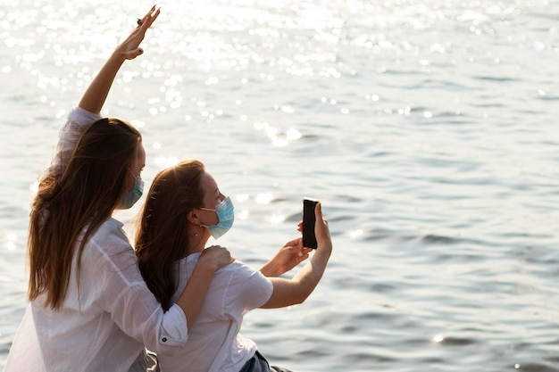 Widok z boku koleżanek z maskami na twarz przy selfie nad jeziorem