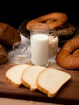 Widok z boku kromki białego chleba na desce do krojenia i szklankę mleka na worze z chlebami i płatkami owsianymi na czarnym tle