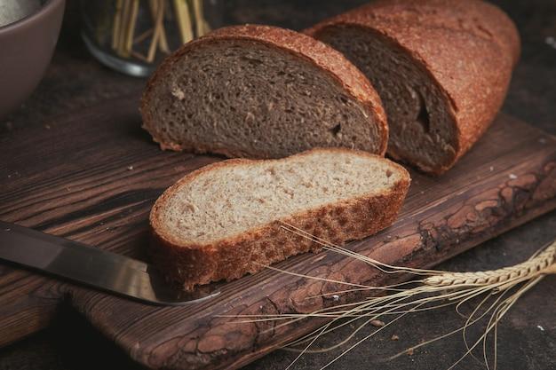 Widok z boku kromki chleba z nożem na desce do krojenia i ciemnobrązowy.