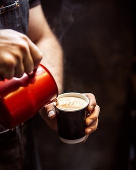 Widok z boku, który mężczyzna czerpie z kremowej filiżanki cappuccino