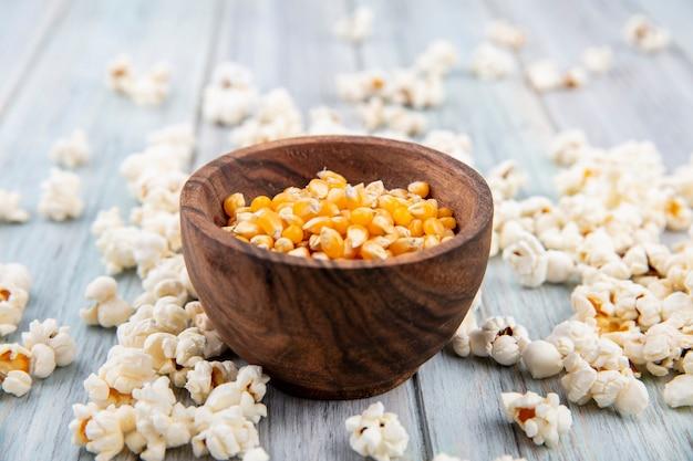 Widok z boku kukurydzy na miskę z popcornem na białym tle na szarej powierzchni drewnianych
