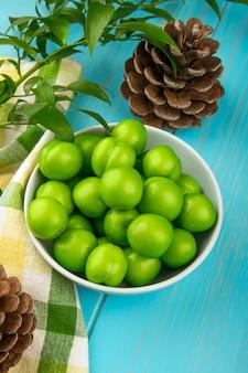 Widok z boku kwaśnych zielonych śliwek w białej misce i stożków na kraciastej tkaninie na niebieskim stole