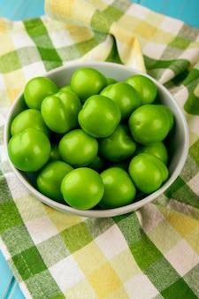 Widok z boku kwaśnych zielonych śliwek w białej misce na stole w kratę