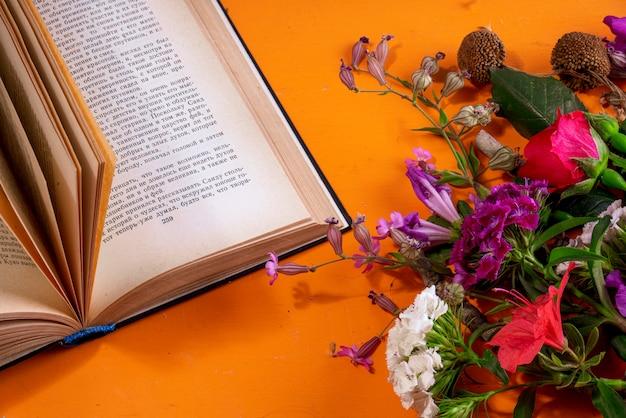 Widok z boku kwiatów i otwarta książka na pomarańczowo