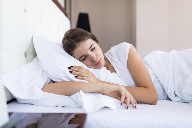 Widok z boku ładnej modelki leżącej rano w łóżku na poduszce, białej pościeli, koncepcji hotelu