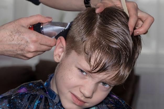 Widok z boku ładny mały chłopiec coraz fryzura przez fryzjera u fryzjera.