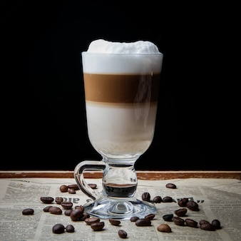 Widok z boku latte z ziaren kawy w starej gazecie