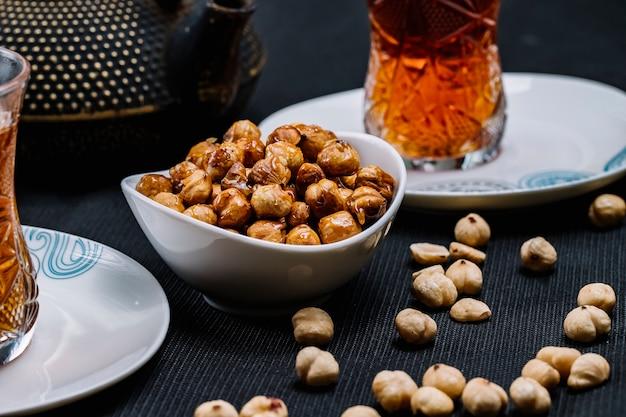 Widok z boku leblebi prażonej ciecierzycy z solą i czarną herbatą na stole