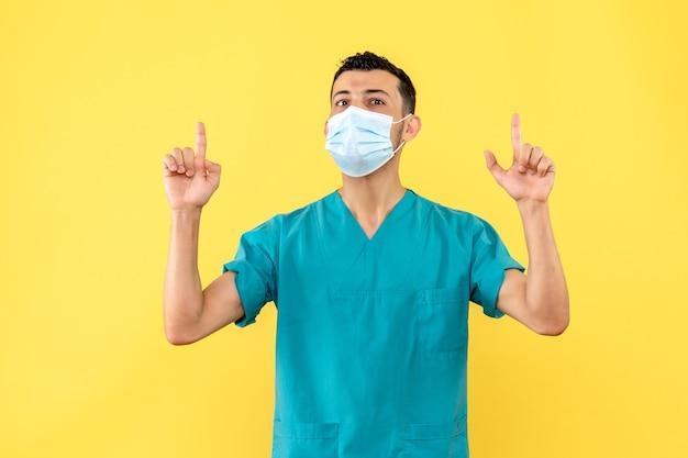 Widok z boku lekarz, lekarz w masce medycznej wskazuje do góry