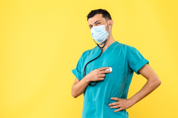 Widok z boku lekarz specjalista chorób zakaźnych z fonendoskopem mówi o masce medycznej