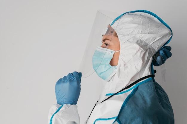 Widok z boku lekarza noszącego odzież ochronną