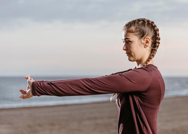 Widok z boku lekkoatletycznej kobiety rozciągającej się na plaży