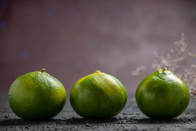 Widok z boku limonki na ciemnym stole trzy zielono-żółte limonki obok gałęzi na szarym stole i na fioletowym tle