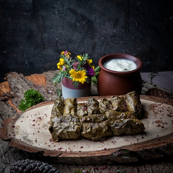 Widok z boku liście winogron dolma faszerowane mięsem i ryżem z sosem śmietanowym na ciemnym drewnianym stole. tradycyjna kuchnia wschodnioeuropejska i azjatycka