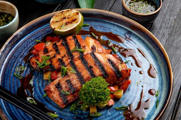 Widok z boku łososia z grilla z warzywami, cytryną i sosem sojowym na talerzu na stół z drewna
