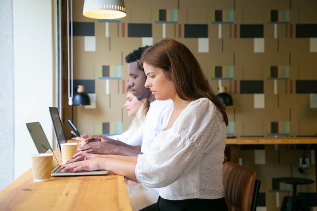 Widok z boku ludzi pracujących na laptopach i siedzących przy stole w pobliżu okna