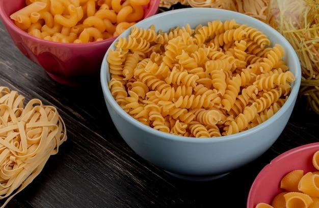 Widok z boku macaronis jako rotini tagliatelle cavatappi rigate i inne na drewnianym stole