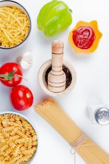 Widok z boku macaronis jako rotli tagliatelle i wermiszel z pomidorami keczup, czosnek, pieprz i sól z czarnego pieprzu na białym stole