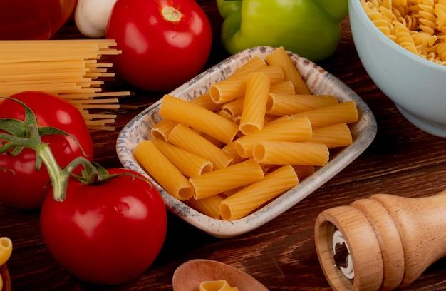 Widok z boku makaronu ziti w misce z spaghetti i rotini typów w misce sól pomidorowa czosnek pieprz na drewnianym stole