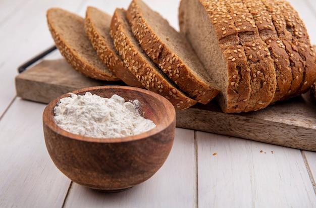 Widok z boku mąki w misce z nasionami brązowej kolby na deska do krojenia na podłoże drewniane