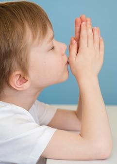 Widok z boku małego chłopca modlącego się